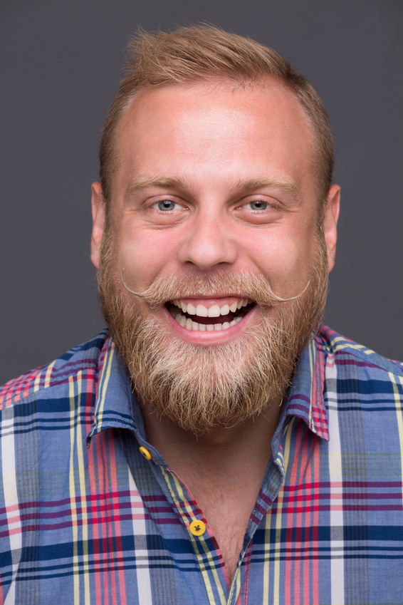 Close-up portrait of laughing bearded man on dark grey. Happy blond man showing his teeth because of being satisfied.